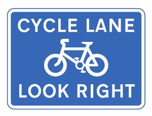 Pedestrians look right for cyclists road sign