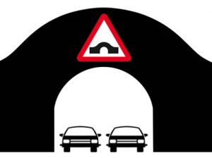 Two cars passing though arched bridge